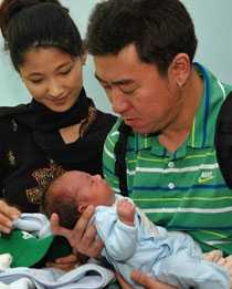 Thomas och Karen Kim från Kalifornien håller sin son som fötts av en kvinna från Calcutta.