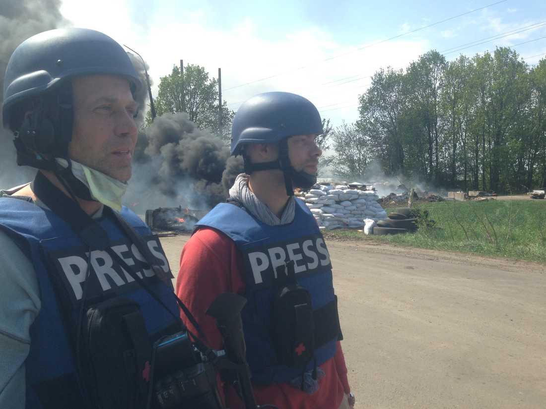 Kriget om barrikaderna Skribenten Mika Velikovskij (till höger) tillsammans med en schweizisk tv-journalist. Den brinnande vägspärren ligger strax utanför Slovjansk nordvästra stadsgräns, intill en enorm nedlagd foderfabrik.