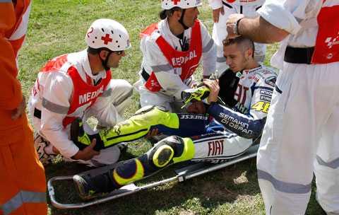 Valentino Rossi tas om hand av medicinsk personal direkt efter olyckan där han bröt högerbenet.