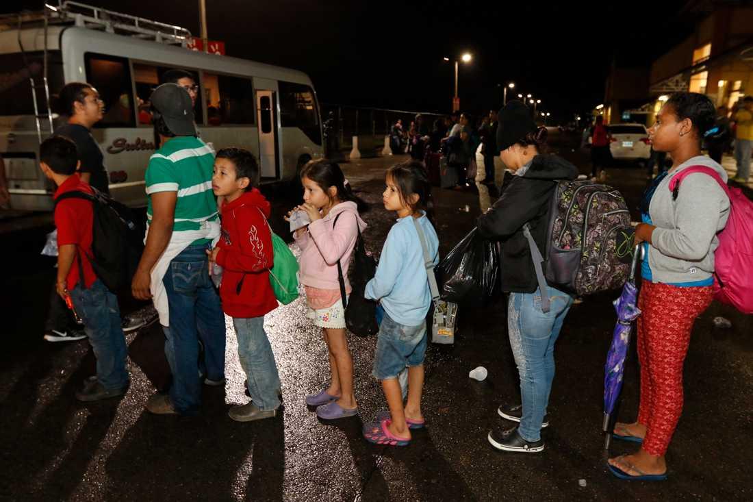 Migranter från Honduras som hoppas kunna ta sig till USA väntar på att få åka buss över gränsen till Guatemala.