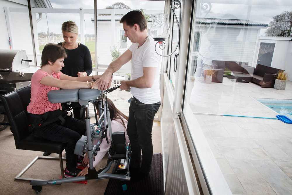 Nicole tränar på att stå upp med hjälp av ett höj- och sänkbart ståbord, en sele, sin pappa Patrik och assistenten Emma.