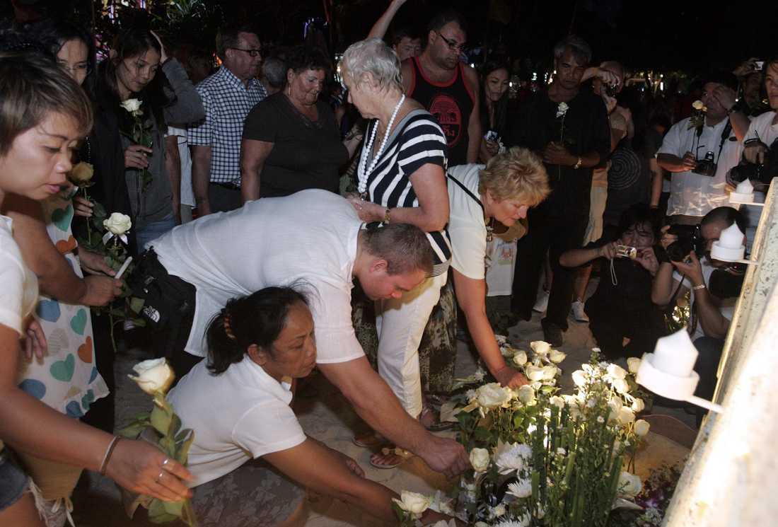CEREMONI I PHUKET Thailändare och turister lägger ner blomor vid Patong beach i Phuket till minne av offren för tsunamikatastrofen för exakt sju år sedan. Över 5000 omkom bara i Thailand.