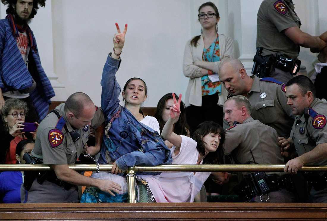 Aktivister som är för abort har låst fast sig i senaten i Austin, Texas, med handklovar.