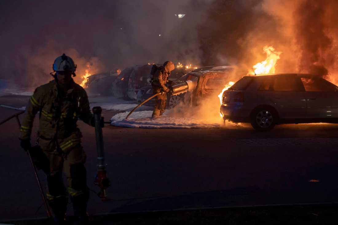 Brandmän släcker de många bilbränderna vid Frölunda torg.