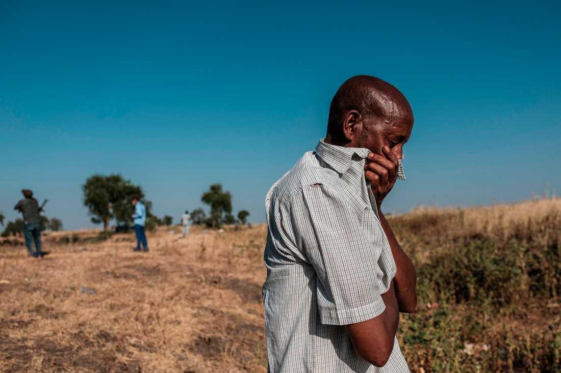 En man står vid ett dike i utkanten av Mai-Kadra i norra Etiopien, där döda kroppar ligger i väntan på att begravas.