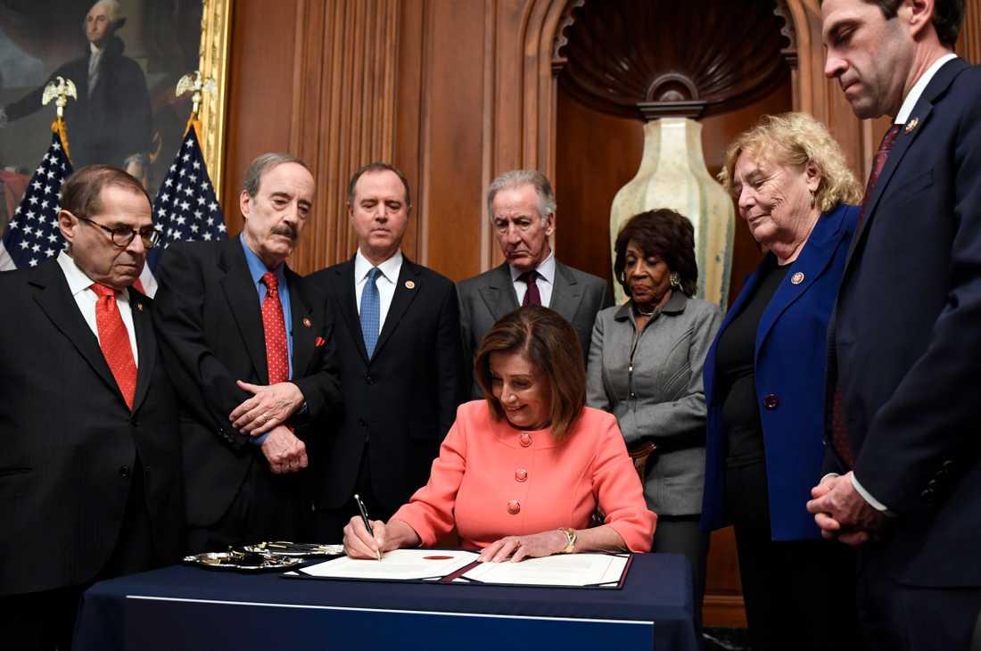 Demokraten Nancy Pelosi, representanthusets talman, undertecknar de formella anklagelserna mot Donald Trump.
