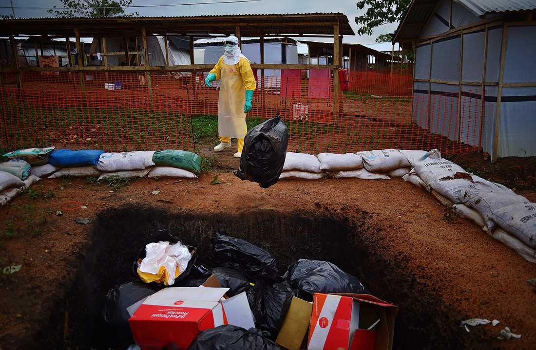 En läkare utan gränser-arbetare slänger kontaminerat material som ska brännas efter att ha varit i kontakt med en ebolasmittad, i staden Kailahun i Sierra Leone.