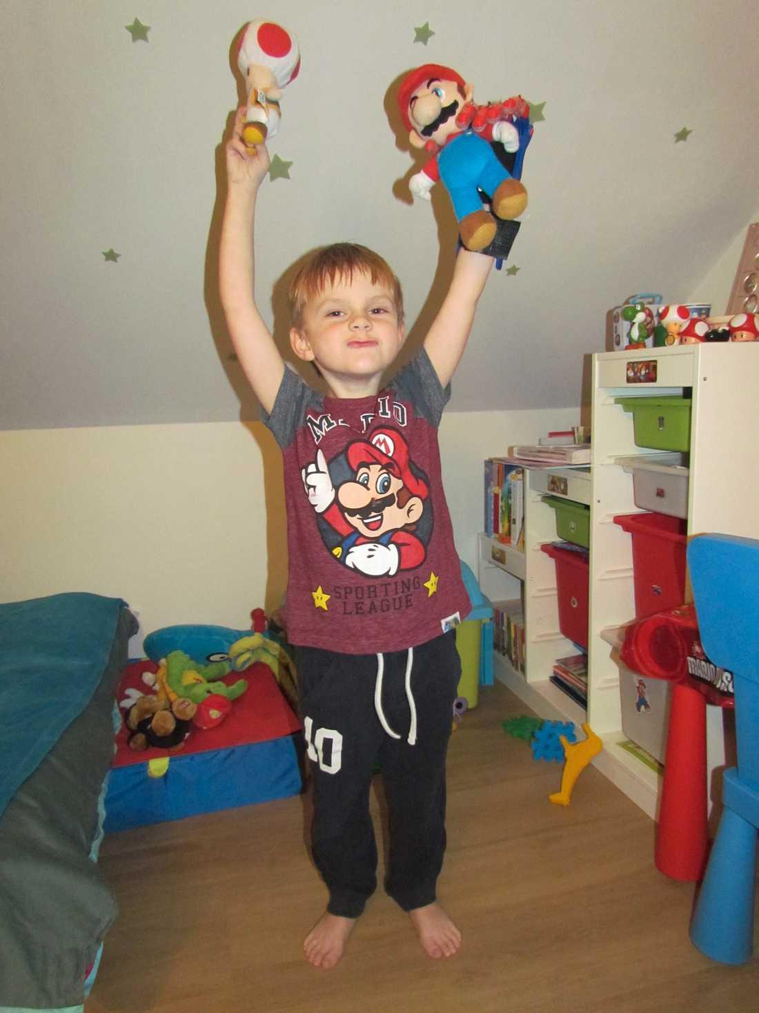 Superglade Antoni med sin superhjälte Antoni, 6, i Polen med sin Super Mario-gubbe. Tack vare den nya 3D-protesen kan Antoni nu greppa en leksak i varje hand.