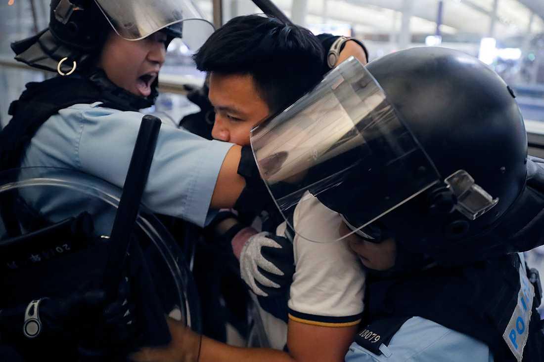 Poliser i kravallutrustning griper en demonstrant under tisdagens tumult på Hongkongs internationella flygplats.