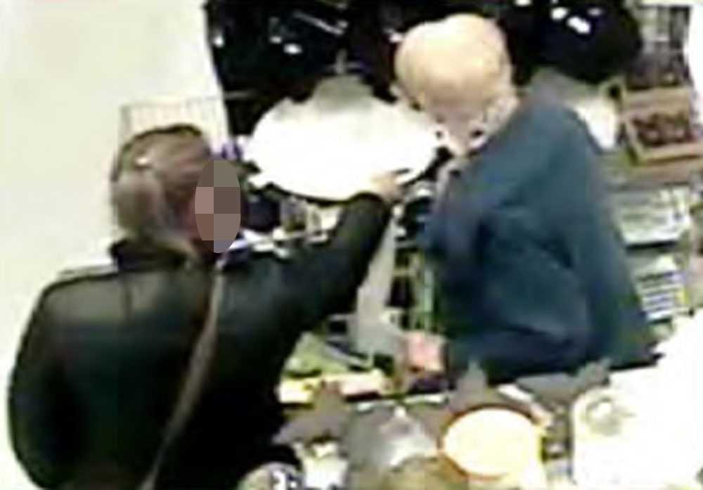 Kvinnan söker upp sitt intet ont anande offer  i butiken. Hon pekar på ett underlägg för att  distrahera den äldre kvinnan.