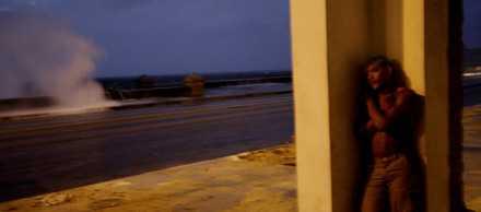 En ung man söker skydd undan vågorna när orkanen Ike svepte in över Kuba på måndagen.