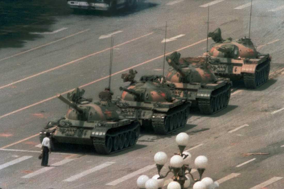 """Den mest kända bilden från demonstrationerna på Himmelska fridens torg är den av mannen som fått smeknamnet """"Tank man"""". Helt ensam stoppar han en lång rad stridsvagnar på en av gatorna vid torget och klättrar till och med upp i en av dem, till synes för att försöka prata med dess förare. Arkivbild."""
