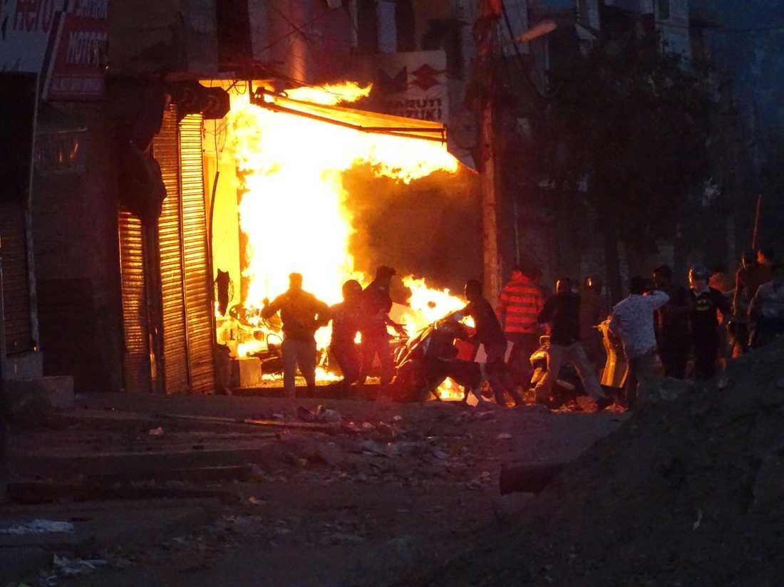En butik sätts i brand av demonstranter under de våldsamma sammandrabbningarna i New Delhi under tisdagen.