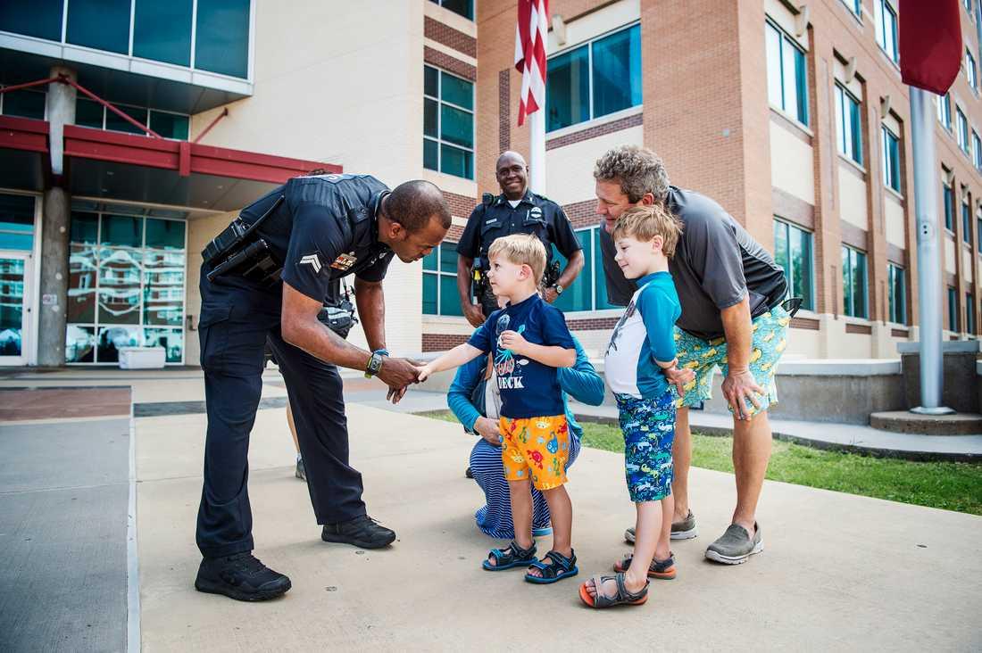 Dallas två dagar efter polisskjutningen. En polis skakar hand med Tate och Holt Foster. Bakom, deras far, Holt Foster.