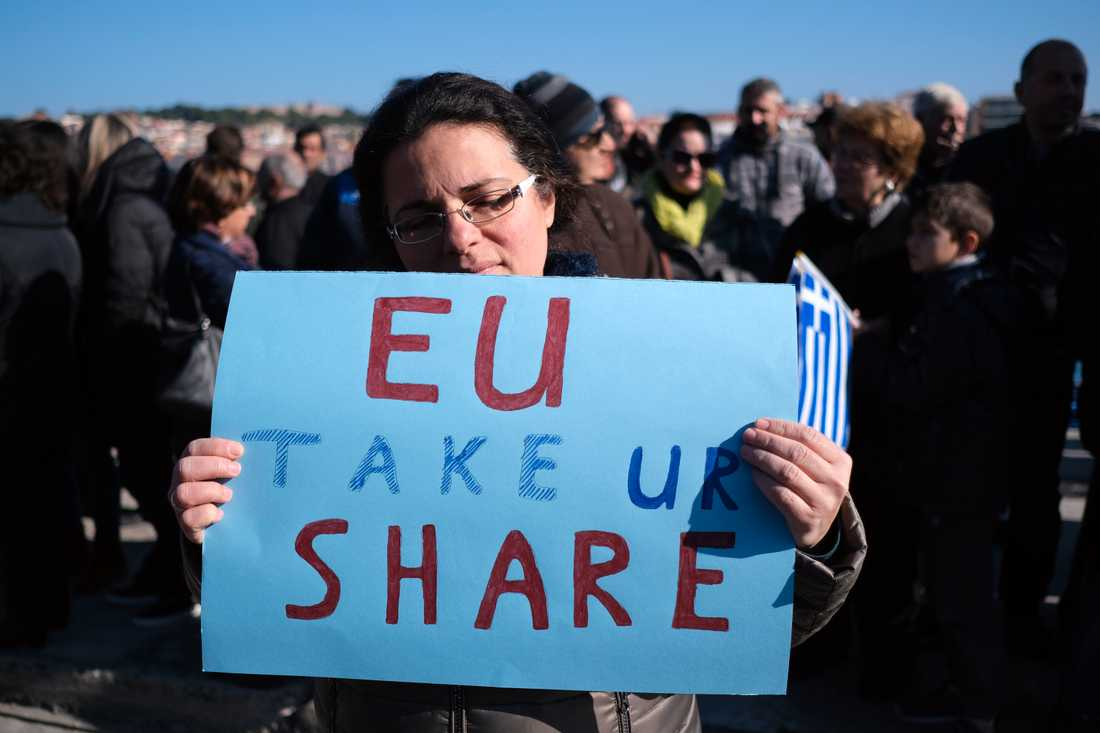 En demonstrant manar EU att ta sitt ansvar under protester på Lesbos mot öns stora flykting- och migrantläger.
