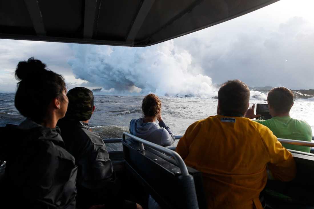 Bild från den 20 maj i år när turister passerar lavan från vulkanen som flyter ner i havet.