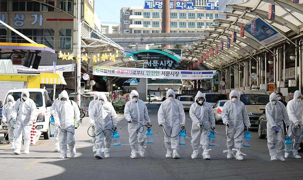 Arbetare i skyddskläder desinficerar ett marknadsområde i Sydkorea.