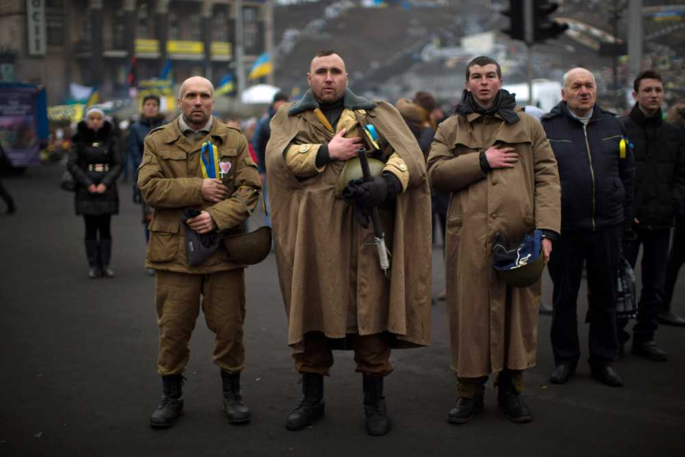 Ukrainska män som kämpade mot ex-president Janukovytj sjunger nationalsången på torget i Kiev, där demonstranter fortfarande samlas.