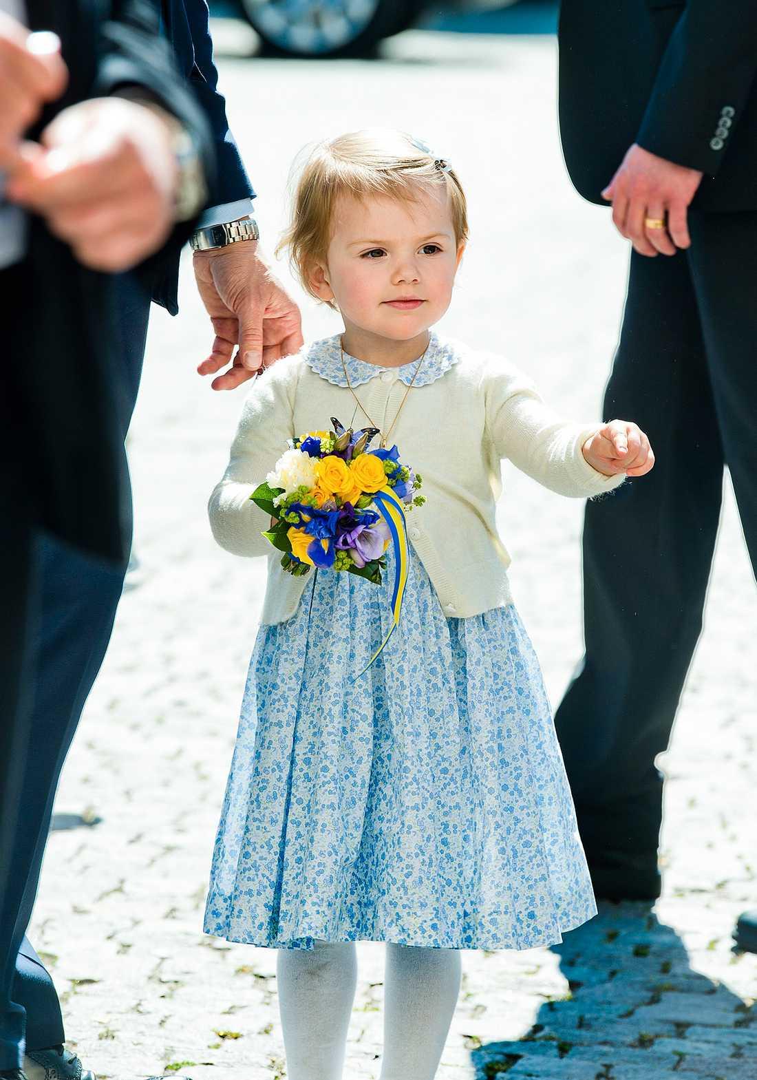 Prinsessan gör sitt första officella uppdrag tillsammans med mamma Victoria och pappa Daniel klädd i blåblommig klänning matchat med citrongul kofta.