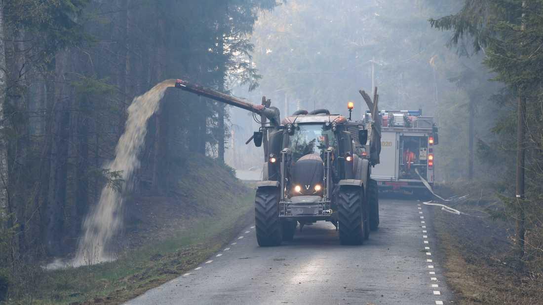 Hästveda tidigare i våras: Med hjälp av traktor och gödseltank vattenbegjuter en av traktens lantbrukare vägarna för att hindra skogsbrandens framfart. Arkivbild.