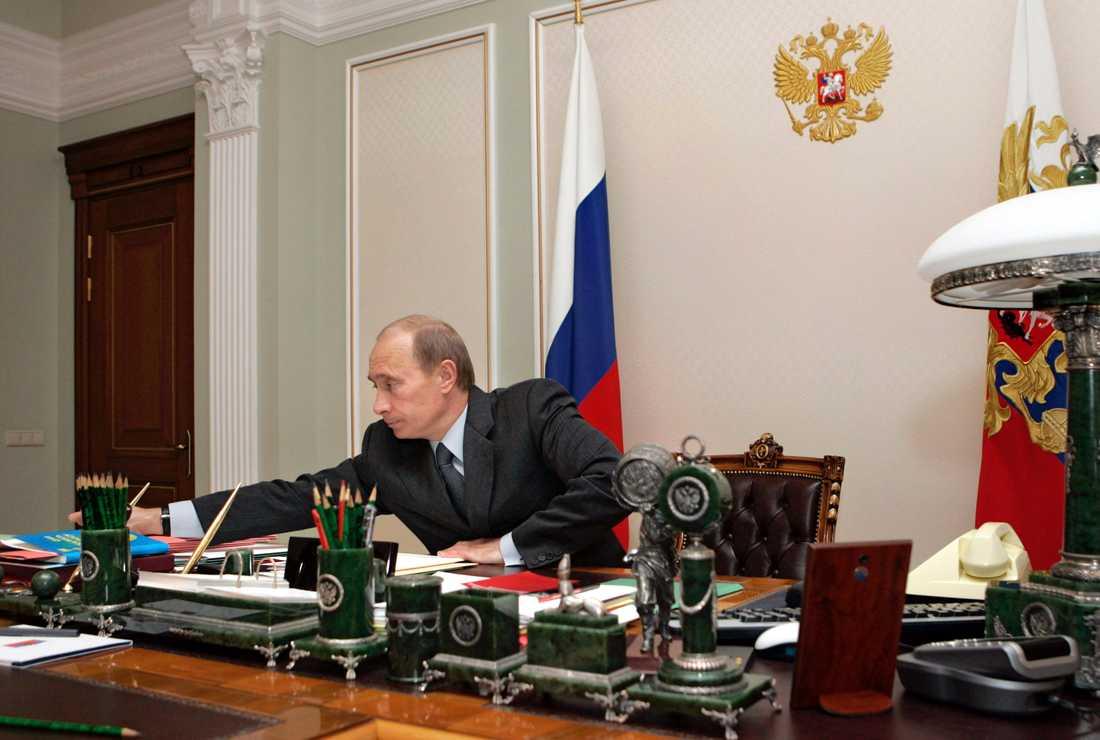 Vladimir Putin, Rysslands president, gillar att visa upp sig när han jagar björn, rider hästar eller flyger med gäss. Men här sitter han vid sitt skrivbord. Ser du hur många pennor har?