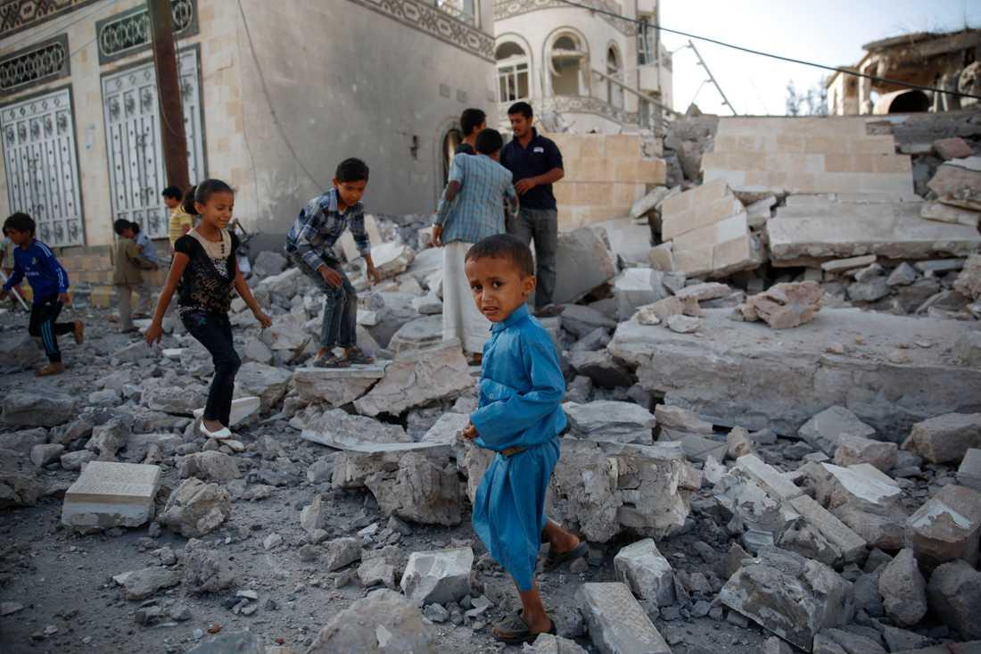 Barnen leker i spillrorna av ett söndersprängt hus i Sanaa, Jemen.