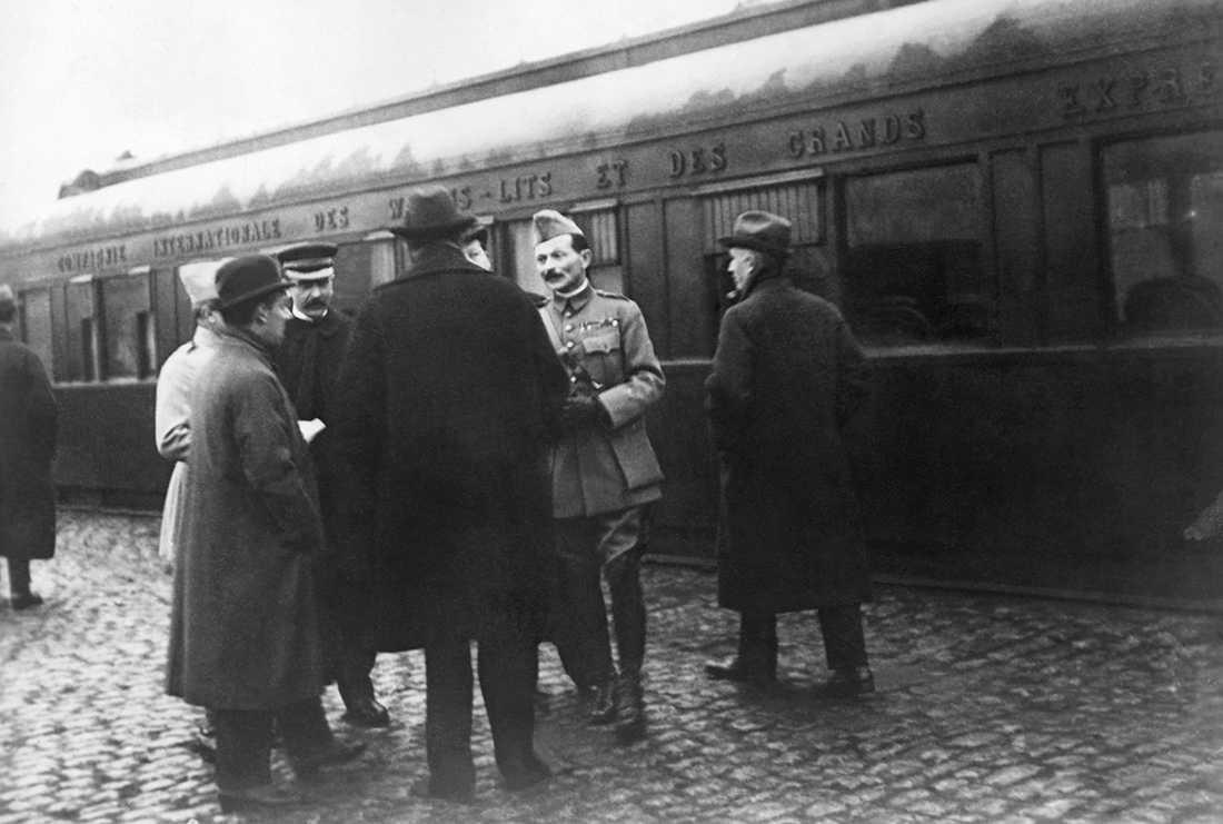 De franska och tyska delegationerna i samspråk framför restaurangvagnen där Tyskland officiellt kapitulerade den 11 november 2018.